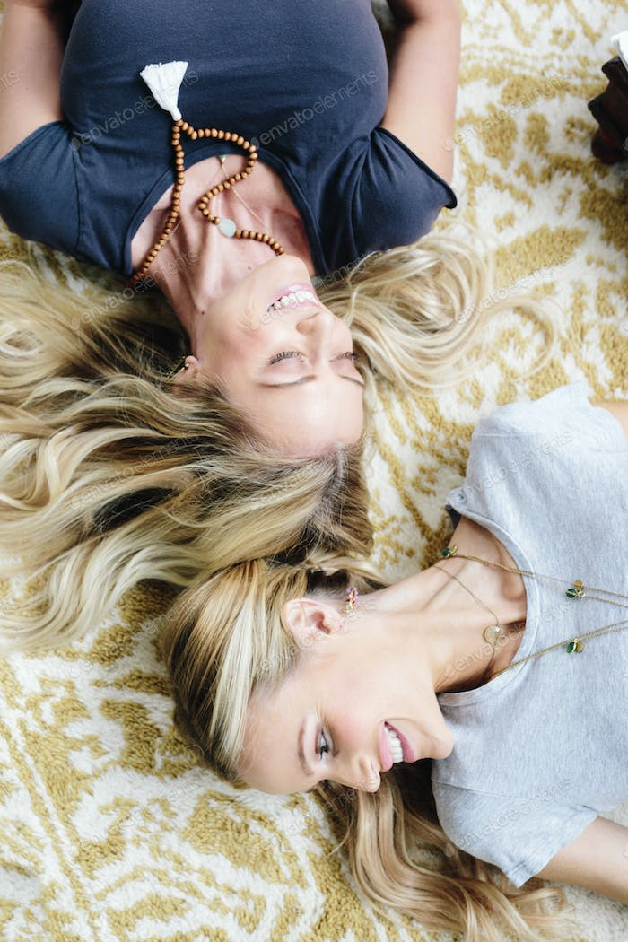 Two women lying on their backs, laughing.