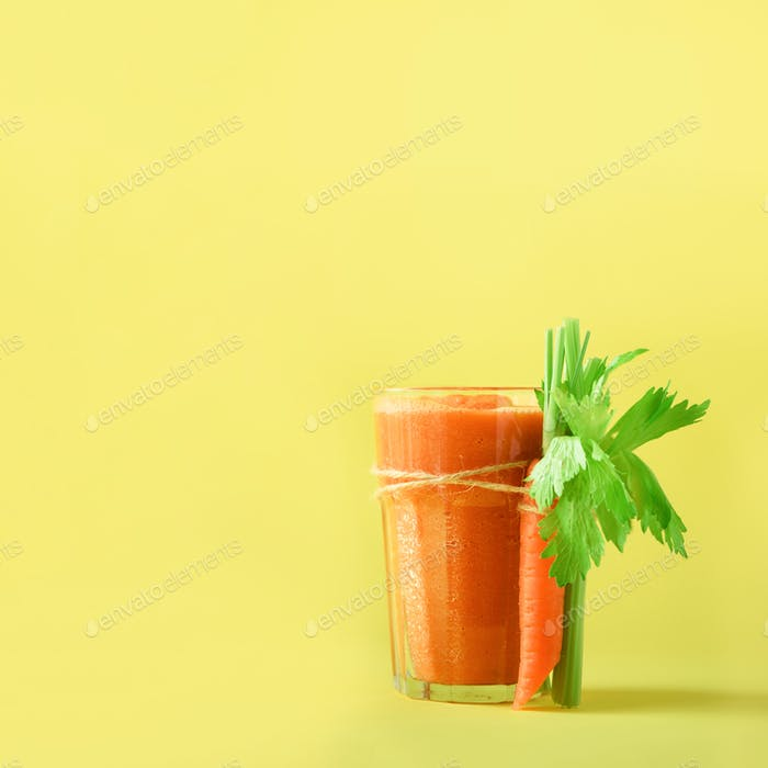 Orange carrot juice with carrots, celery on yellow background. Square crop. Fresh vegetable smothie