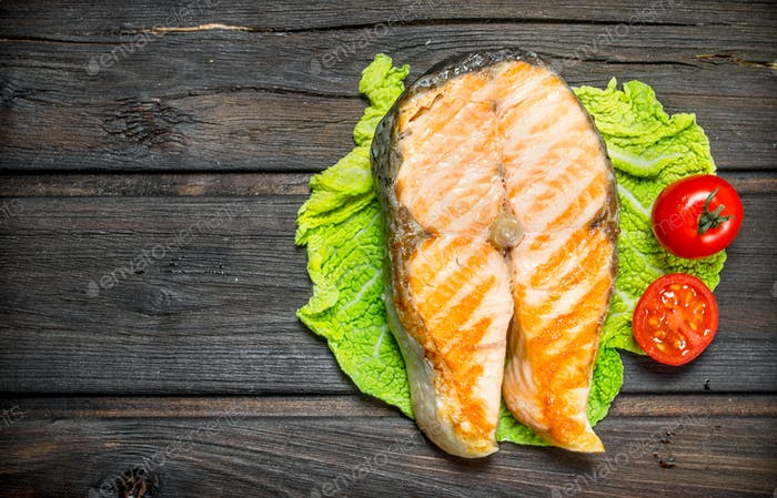 Grilled salmon steak on a lettuce leaf .