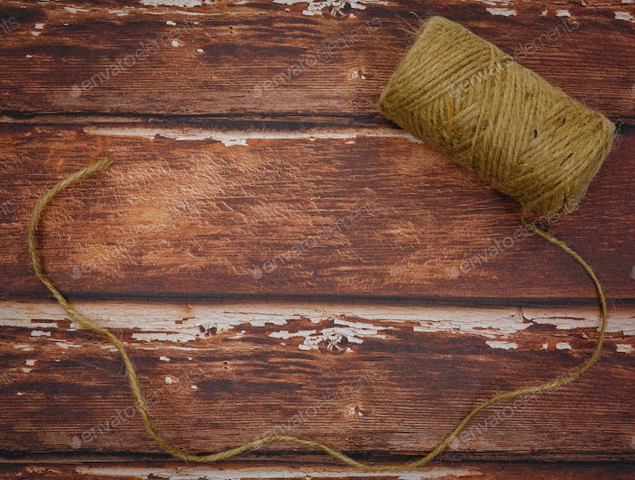Rough thread reel on wood background