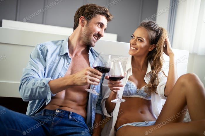 Beautiful couple is smiling and hugging while spending time together in bedroom
