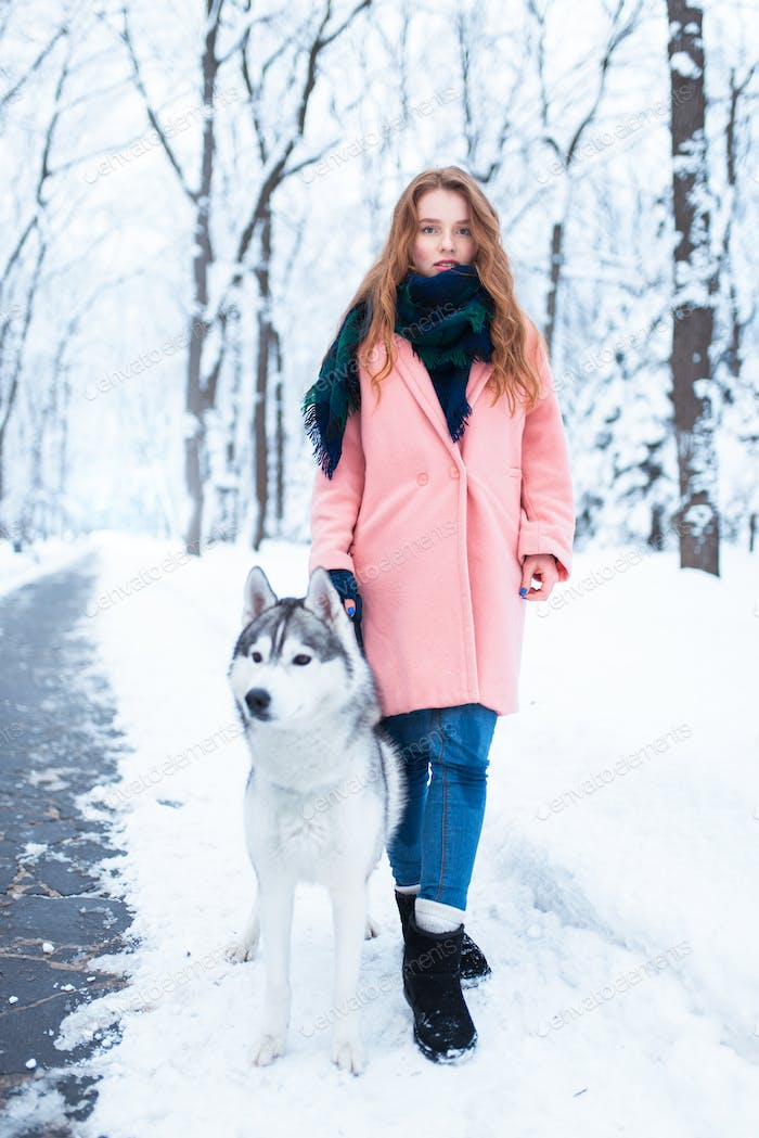 Portrait of young woman with husky dog