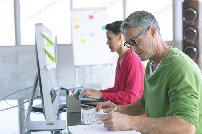 Side view of Multi-ethnic business people working on computer at desk in modern office