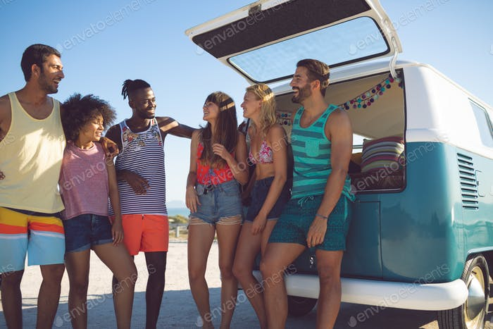 Front view of happy group of diverse friends interacting with each other near camper van at beach