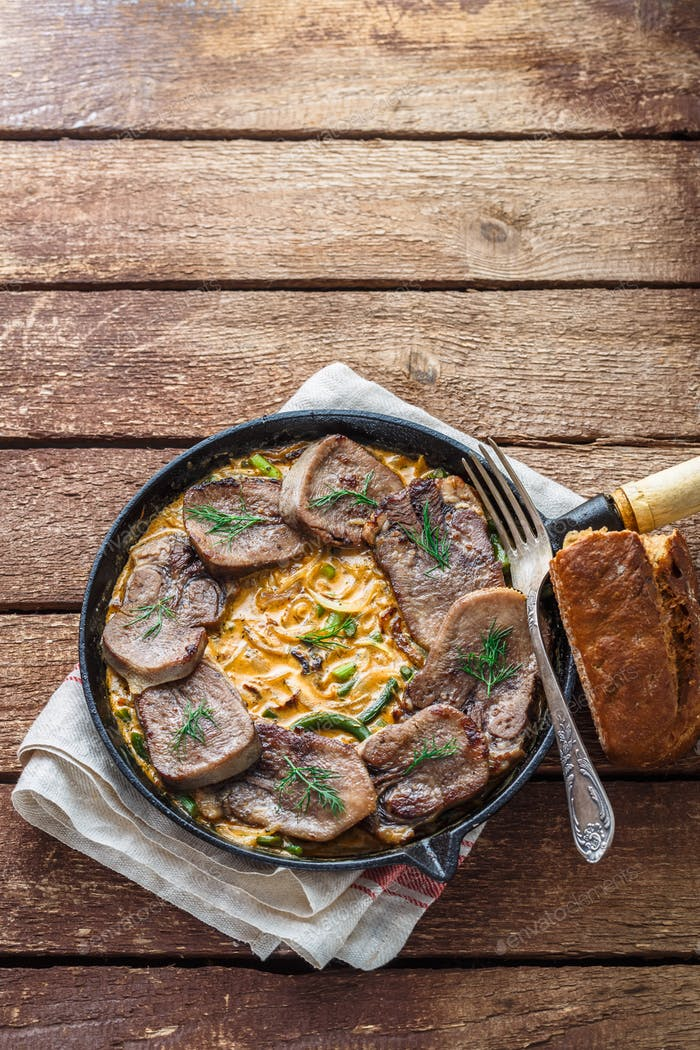 Sliced beef tongue in cast iron skillet, copy space
