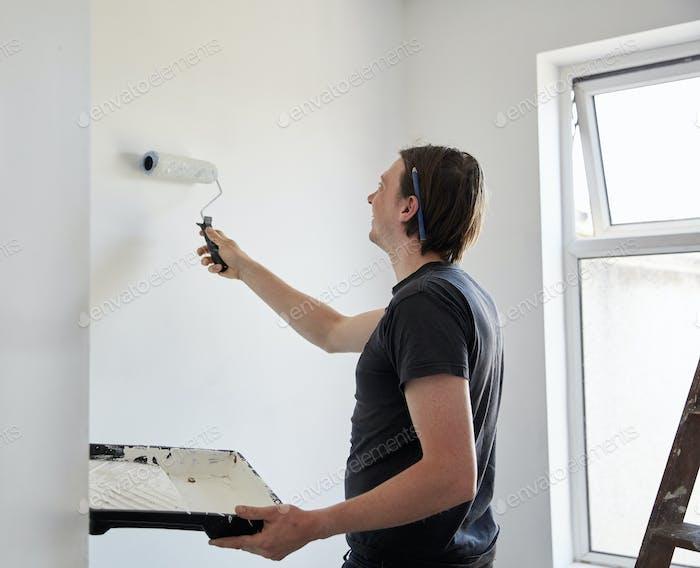 Художник и декоратор, используя валик для краски и удерживая поддон для краски, украшая комнату.