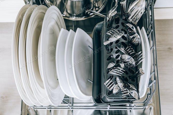 Lavavajillas abierto con platos limpios de primer plano después del lavado.