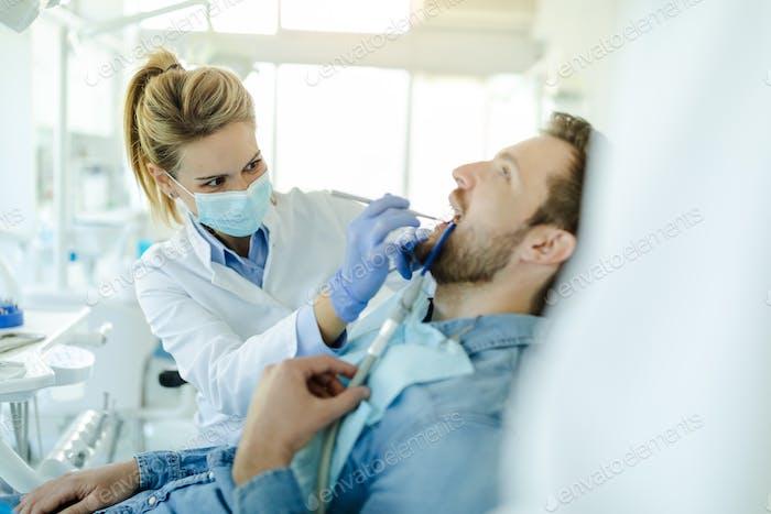 El joven visita la clínica de odontología para el tratamiento profesional de los dientes.