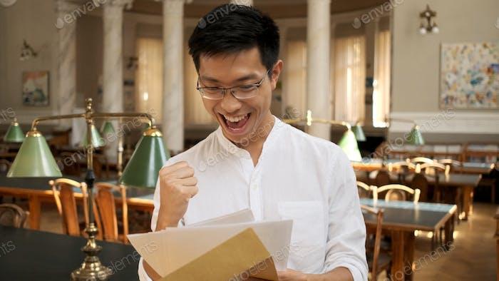 Porträt asiatischer Student freudig öffnen Umschlag mit Prüfungsergebnissen in der Universitätsbibliothek