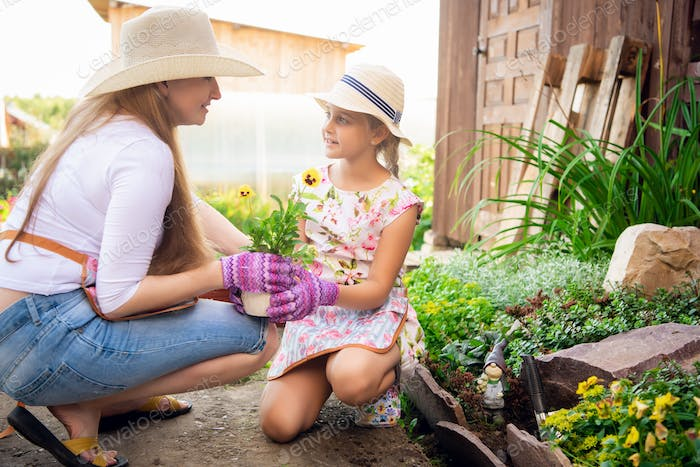 A young woman with a small daughter is planting a plant in a pot