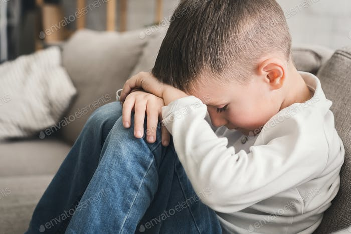 Crying child boy hugging his knees on sofa