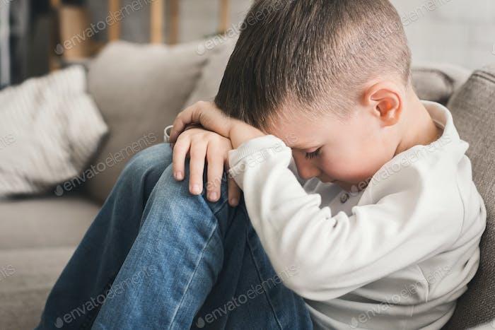 Weinen Kind Junge umarmt seine Knie auf Sofa