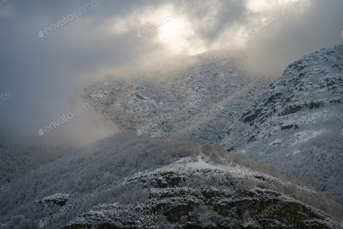 Low clouds interact with the snowy mountains