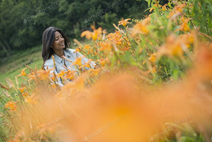 A woman standing among flowering plants on a farm.