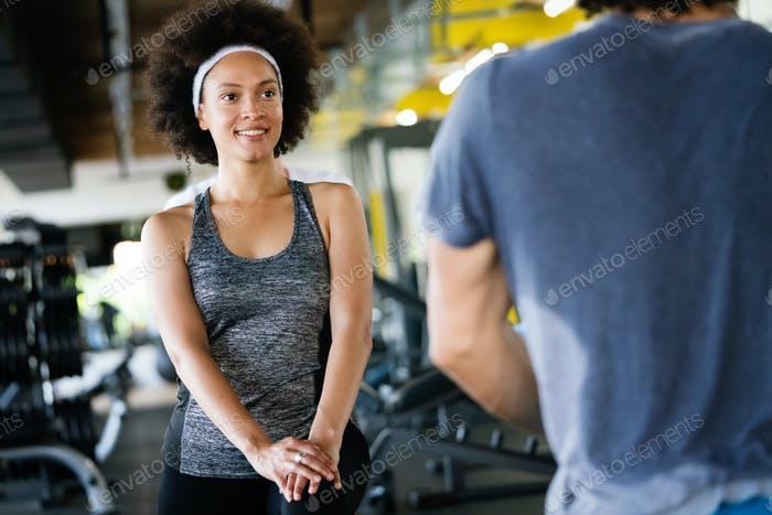 Young fit man doing exercises with personal trainer in gym