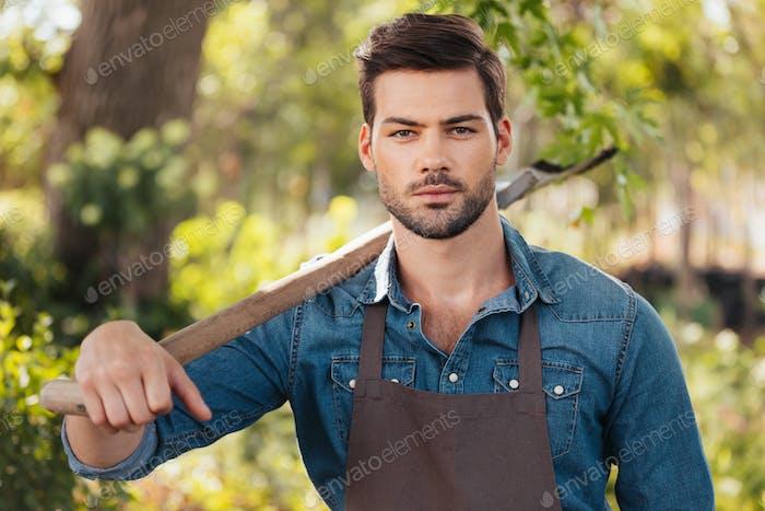 portrait of handsome gardener with spade on shoulder looking at camera in garden