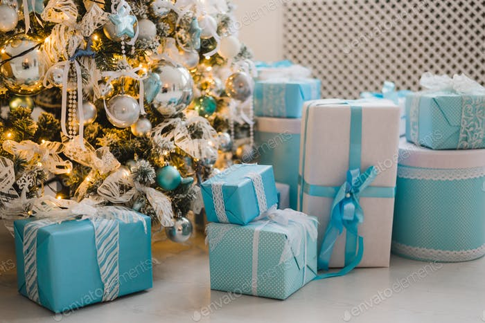 Christmas gifts under the decorated tree in blue