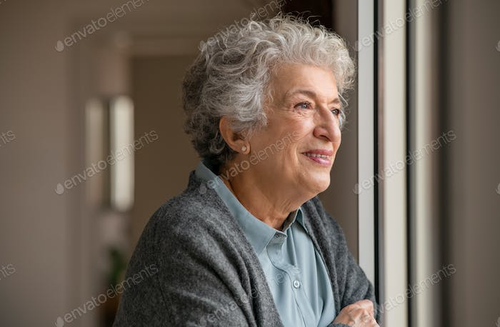 Happy senior woman looking out of the window at home