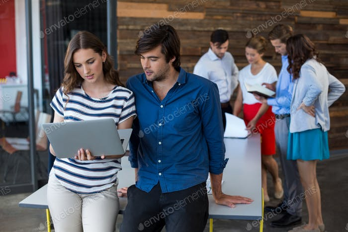 Male and female business executives using laptop