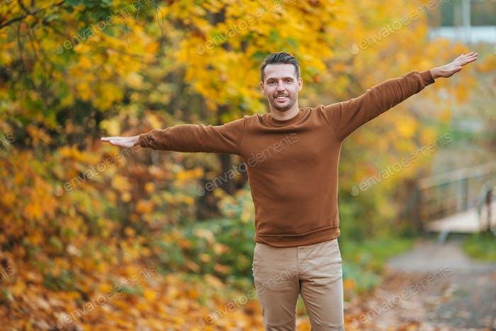 Junger Mann im Herbst Park im Freien breitete seine Arme