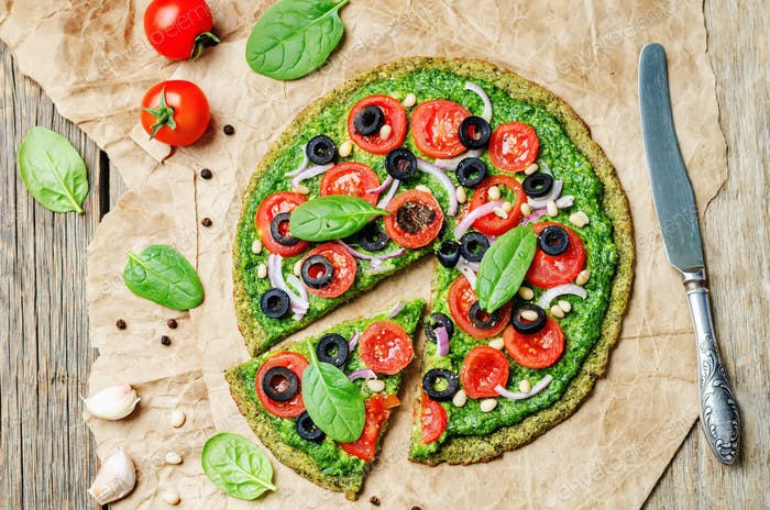 vegan broccoli zucchini pizza crust with spinach pesto, tomatoes