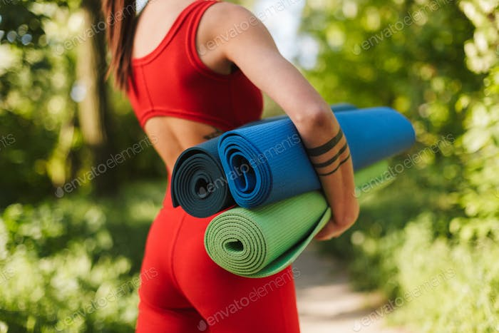 Young woman body in red jumpsuit standing from back with colorful yoga mats in hands in park