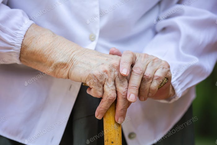 Senior woman's hands holding walking stick