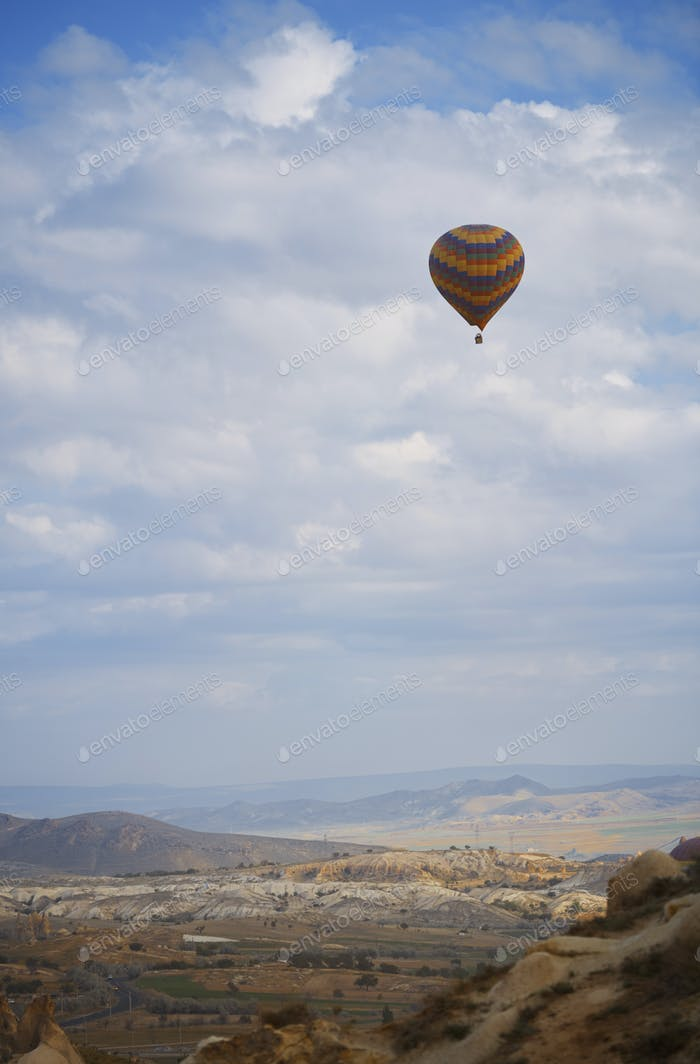 Hot Air Balloon Flying Over the Rocky Land