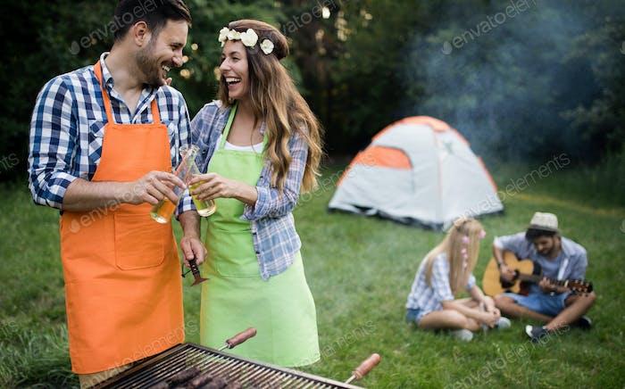 Gruppe von glücklichen Freunden mit Grillparty im Wald