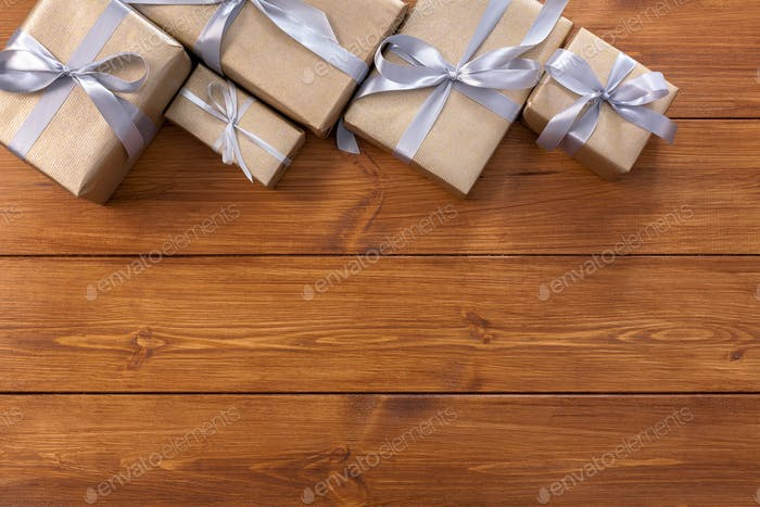 Presents in gift boxes on wood frame background