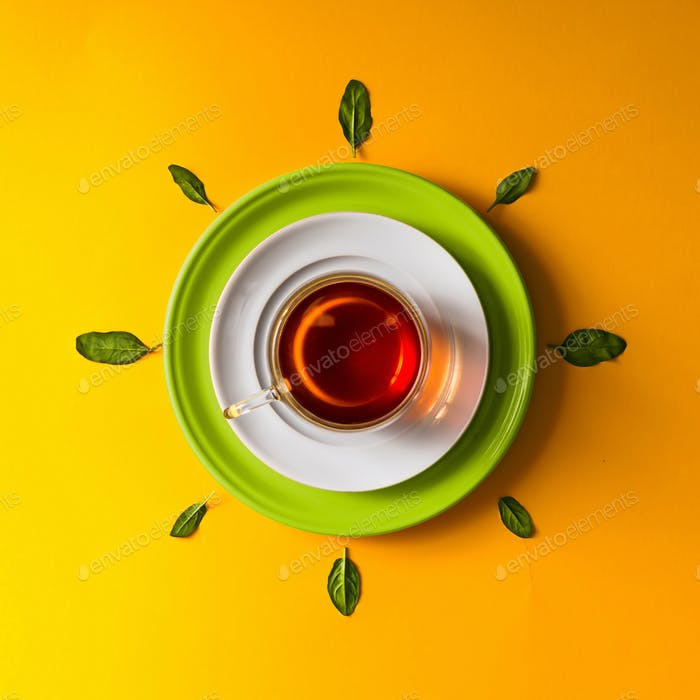 Tea in glass cup with green leaves  on orange background.