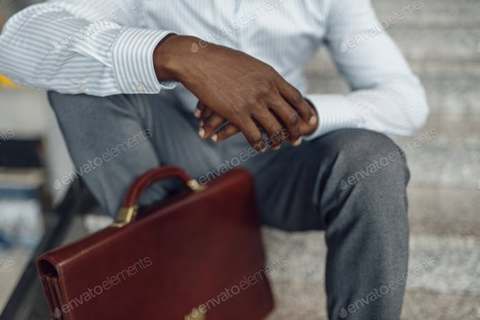 Black businessman with briefcase sitting on stairs