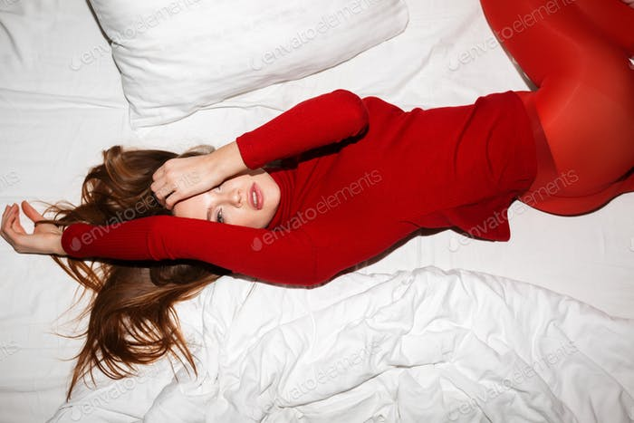 Beautiful lady in red sweater and tights lying in white bed and dreamily looking in camera