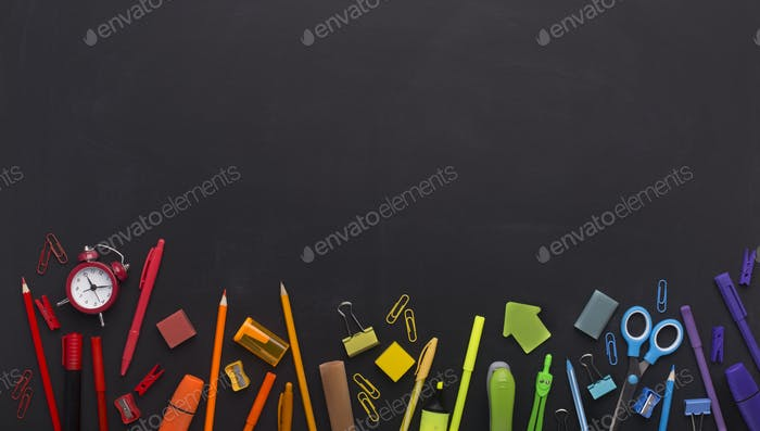 Rainbow of school stationery with copy space above