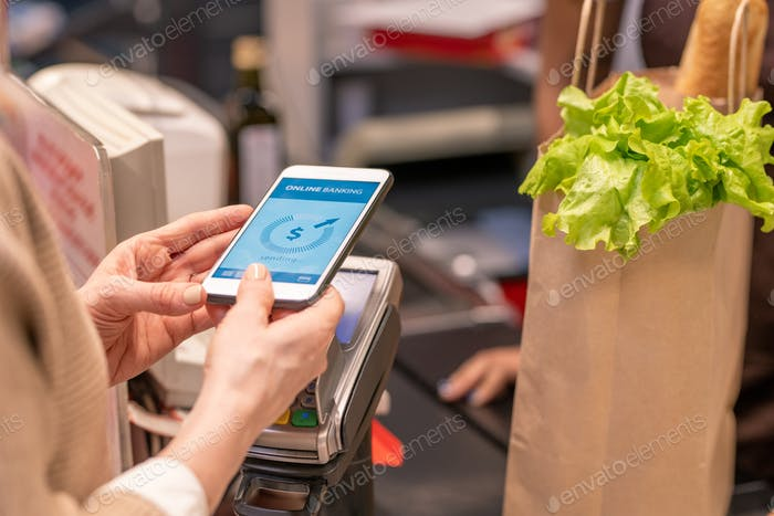 Hands of contemporary mature customer with smartphone over payment machine