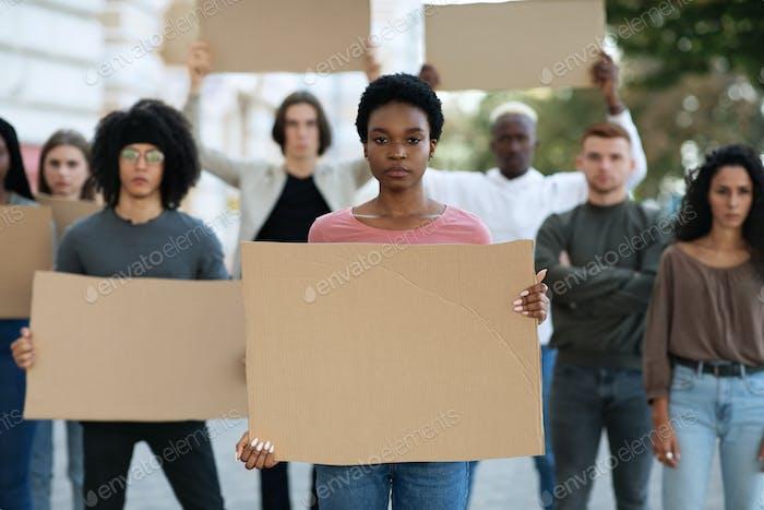 Señora negra liderando un grupo de manifestantes en la calle