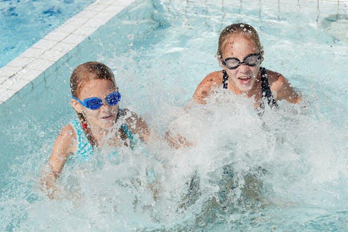 Zwei glückliche Kinder spielen auf dem Schwimmbad am Tag Zeit.