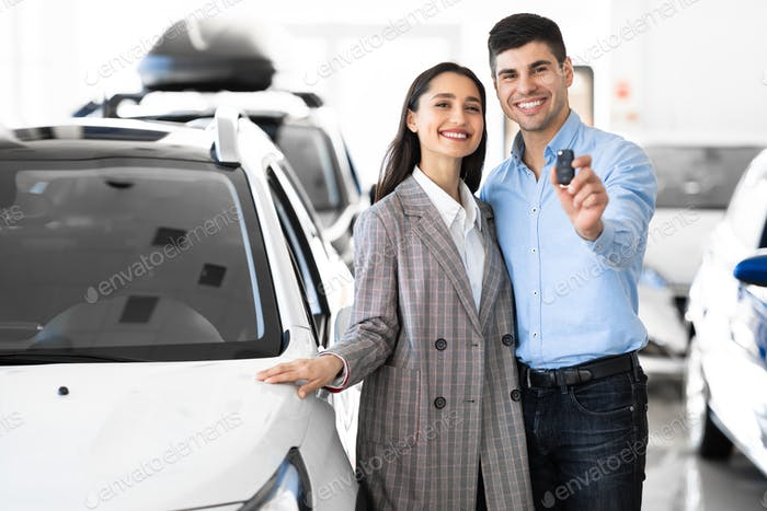 Family Showing Car Key Standing In Dealership Store