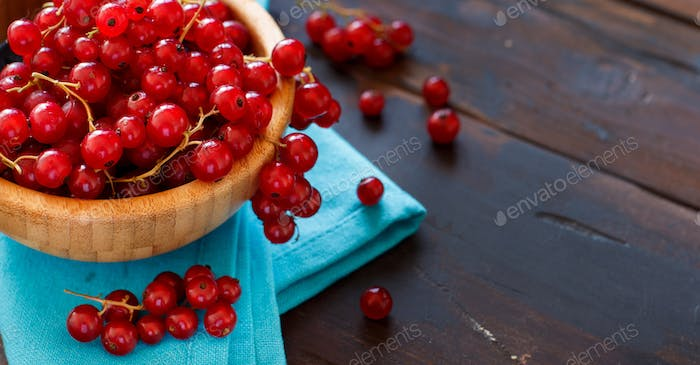 Ripe red currant berries in a bowl on a blue napkin
