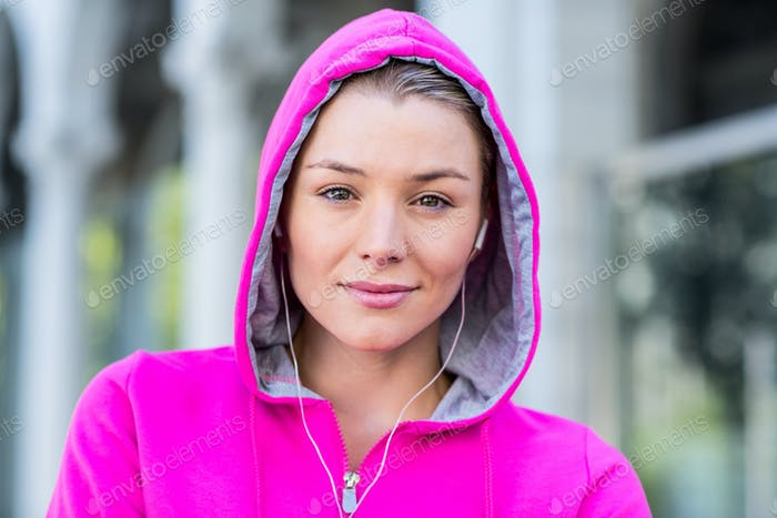 Portrait of a woman wearing a pink jacket putting her headphones on a sunny day