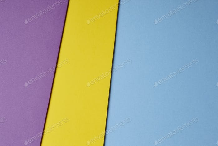 Colored cardboards background in blue yellow purple tone. Copy space. Horizontal