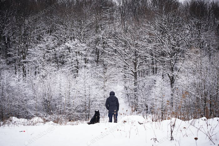Man walking with his dog in winter forest