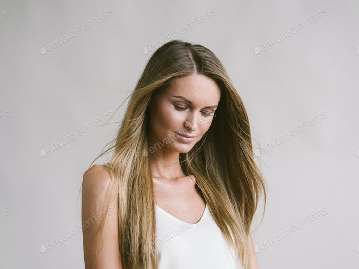 Beautiful woman natural portrait girl with long blonde hair over white gray wall