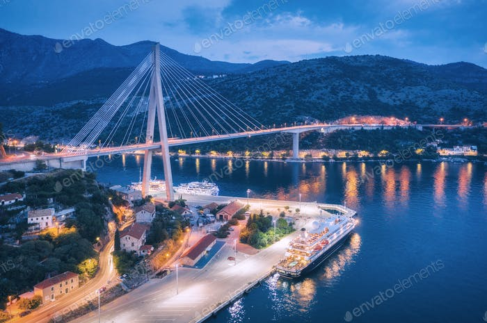 Aerial view of cruise ship in port and beautiful bridge at night
