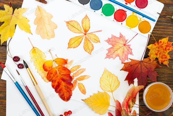 Watercolor painting with autumn leaves, paint, brushes and color