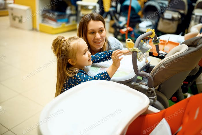 Mother and little daughter buying baby stroller