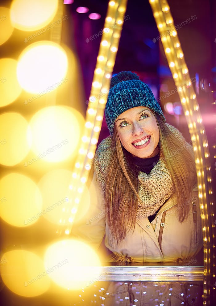 Portrait of a young woman in winter clothing enjoying christmas lighting in Vigo