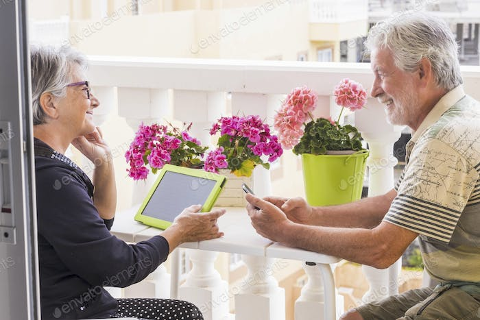 two adults people use mobile technology internet outdoor in the home terrace