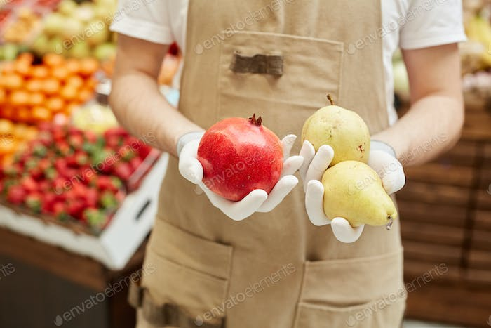 Merchant Holding Fruits at Market Stand