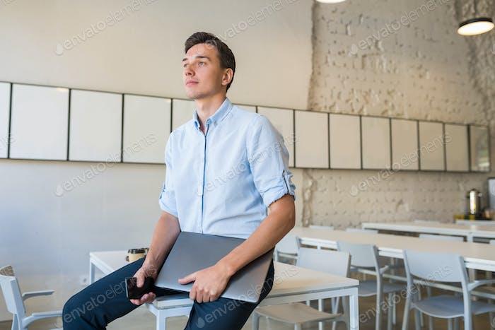 glücklicher junger attraktiver lächelnder Mann sitzt im Büro im Coworking und hält Laptop